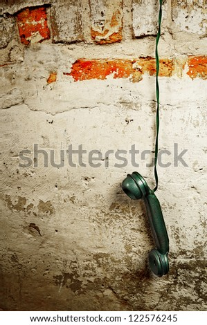 Retro Phone Cord - Vintage Telephone Handset Receiver hanging by the Cord down a Brick Wall - stock photo