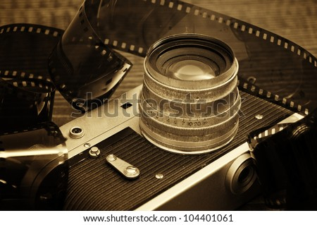 Retro photo camera on a wooden table plate with some 35 overexposed film strip - stock photo