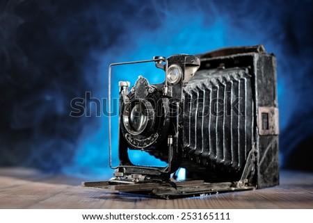 Retro photo Camera on wooden table. Shallow depth of field. - stock photo