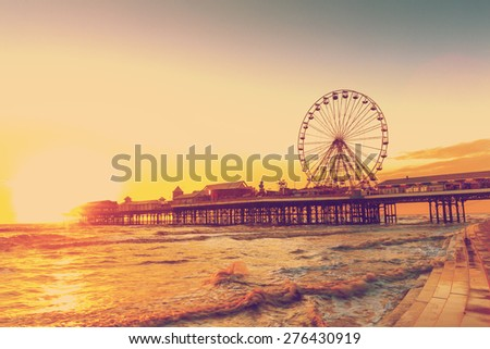 RETRO PHOTO FILTER EFFECT:  Blackpool Central Pier at Sunset with Ferris Wheel, Lancashire, England UK - stock photo