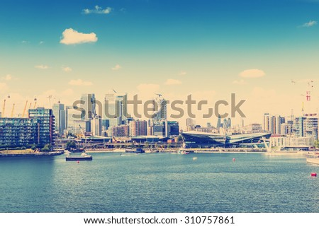 RETRO PHOTO FILTER EFFECT: View of the City of London and Isle of Dogs from The Victoria Docks, London, England, UK - stock photo