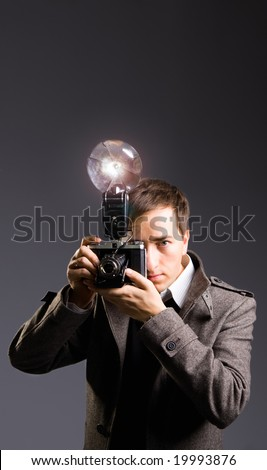 Retro photo journalist holding vintage camera with flash bulb - stock photo