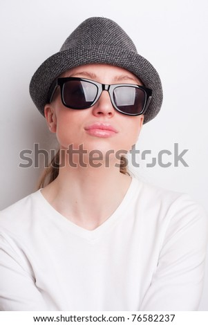 Retro photo of a girl in sunglasses and an old hat - stock photo