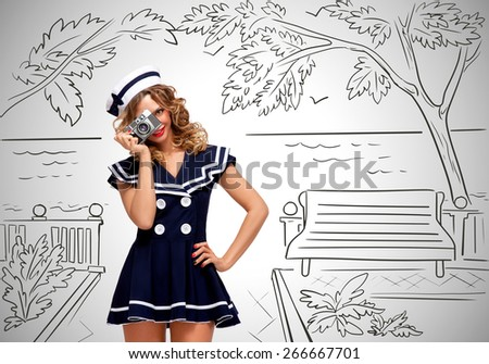 Retro photo of a glamorous pin-up sailor girl walking along the esplanade and taking a photo of nature with an old vintage photo camera on grey sketchy background. - stock photo