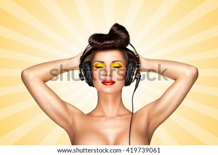 Retro photo of a nude pin-up girl with big vintage music headphones on colorful abstract cartoon style background. - stock photo