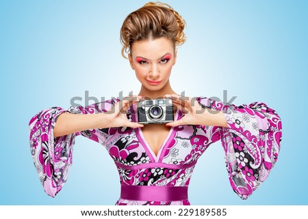 Retro photo of a smiley fashionable hippie homemaker, holding an old vintage photo camera with two hands and showing emotions on blue background. - stock photo