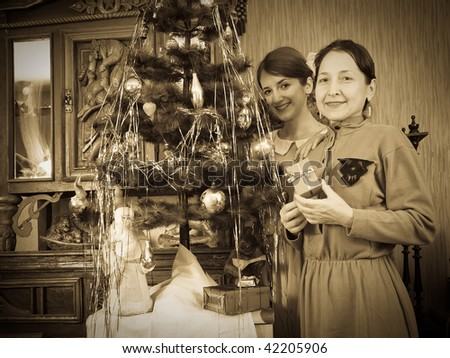 Retro photo of  daughter with mother near Christmas tree at home