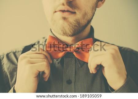 Retro photo of fashion businessman correcting red bowtie - stock photo