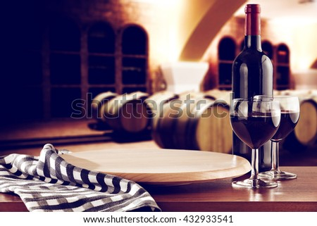 retro photo of few barrels and blue and white napkin bottle and wine in glasses  - stock photo