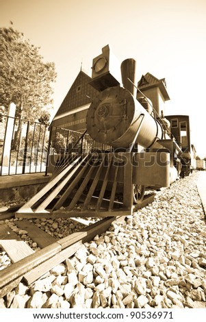 Retro photo of old steam locomotive at railway station - stock photo