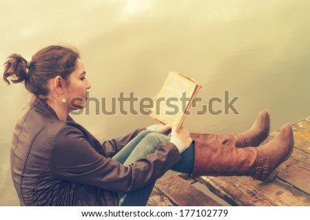 Retro photo of young woman reading a book - stock photo