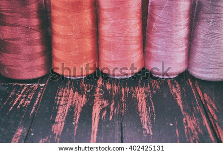 Retro photo thread spools in red scale sewing and needlework on the background of the old wooden table - stock photo