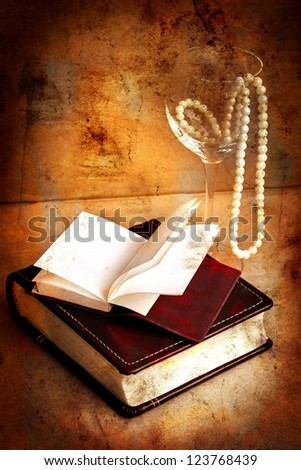 retro picture of a necklace lying on a book/ /romantic vintage background with  and blank page