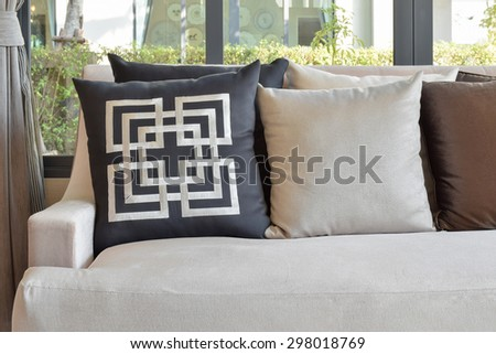 Retro pillows on the cozy brown sofa in the living room - stock photo