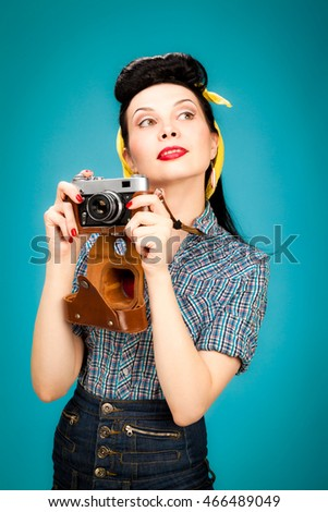 Retro pin-up woman with film camera on blue background