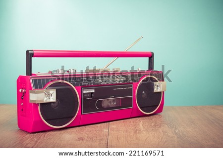 Retro pink radio cassette stereo recorder on wooden desk - stock photo