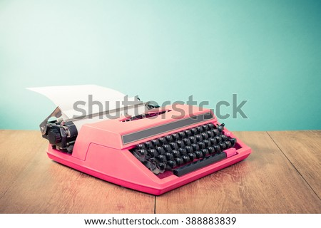 Retro pink typewriter with paper on wooden table front mint green background. Vintage old style filtered photo