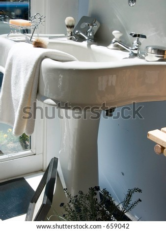 Retro porcelain pedestal sink filled with shaving goodies, towels and cleaning items from the era. - stock photo