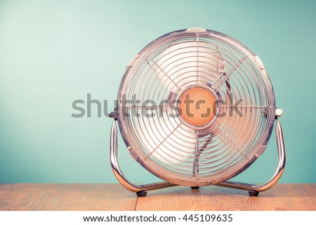 Retro portable office or home cooling fan in working mode standing on table. Vintage instagram style filtered photo - stock photo
