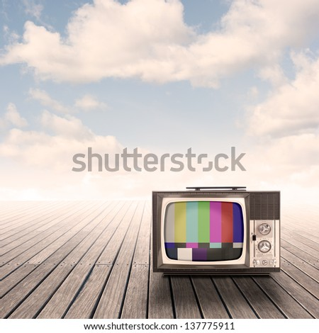 retro portable television on pier with sky on sunset - stock photo