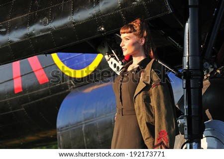 retro portrait of a beautiful lady dressed in Canadian WWII uniform with a bomber aircraft - stock photo
