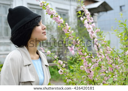 Retro portrait of a beautiful woman smelling spring flowers. Vintage style. Outdoor fashion photo. Female beauty.