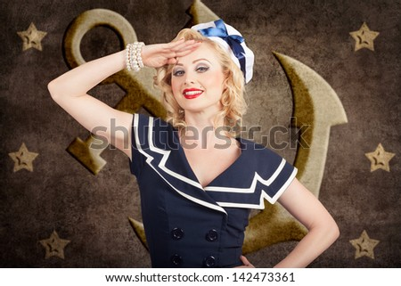 Retro portrait of a beautiful young blond woman wearing navy hat saluting in pin-up fashion in front of old anchor background. American sailor style - stock photo