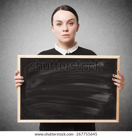 Retro portrait of a strict young woman holding a blackboard - stock photo