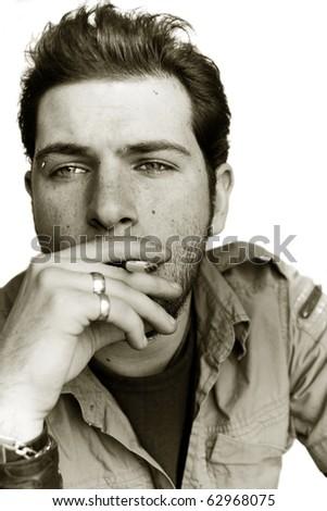 Retro portrait of a young man smoking a cigarette. Sepia toned image. - stock photo
