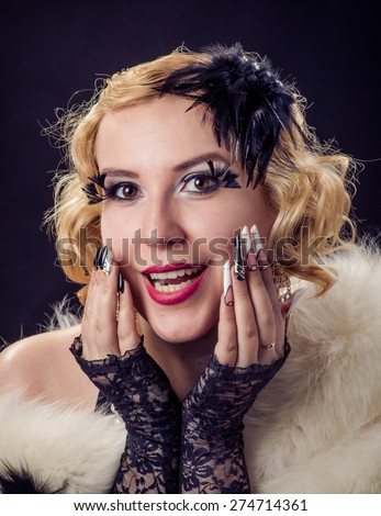 Retro portrait of beautiful happy blonde wondering smiling woman with jewels and extreme long nails. Gatsby, Vintage style. Isolated on black background