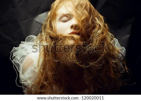 Retro portrait of red-haired (ginger) queen like girl over wrinkled black paper background. studio shot - stock photo