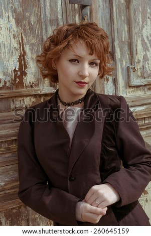Retro portrait of red haired women in vintage coat agains obsolete wooden background. - stock photo