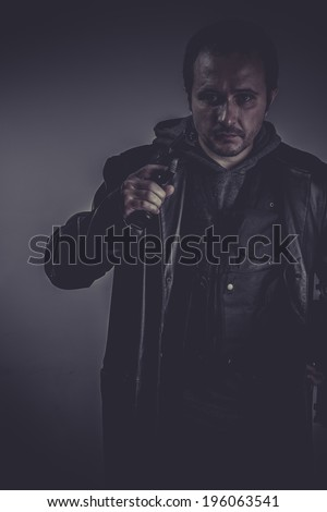 retro portrait of stylish man with long leather jacket, gun armed - stock photo