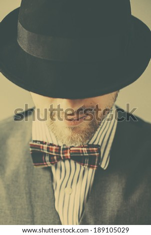 Retro portrait of young business man in hat and bowtie - stock photo