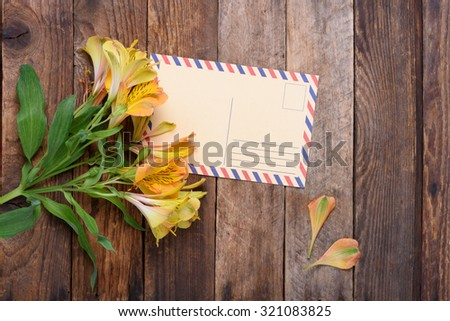 Retro postcard with flowers on vintage wooden table still life - stock photo