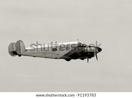 Retro propeller airplane in leveled flight - stock photo