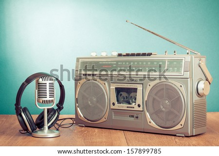 Retro radio and cassette player, headphones, microphone on table in front mint green background - stock photo