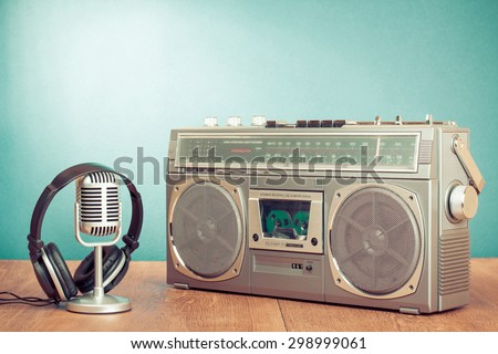 Retro radio cassette recorder, headphones and microphone on table in front mint green background. Old instagram style filtered photo - stock photo
