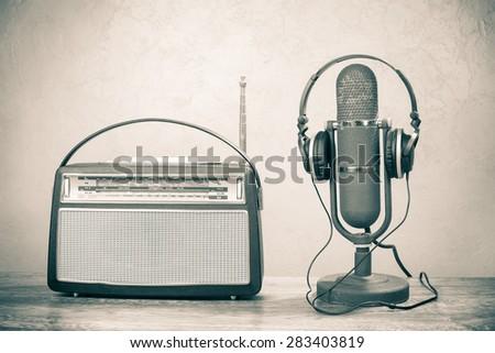 Retro radio from 60s, old ribbon studio microphone and headphones. Vintage style sepia photo - stock photo