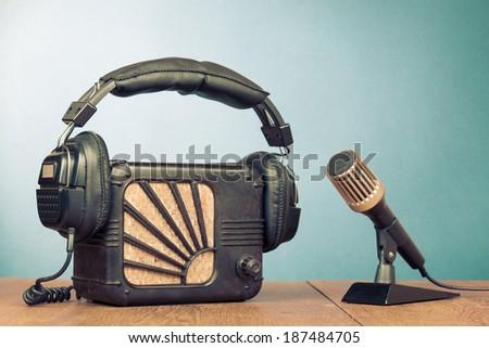 Retro radio, headphones and microphone on table - stock photo