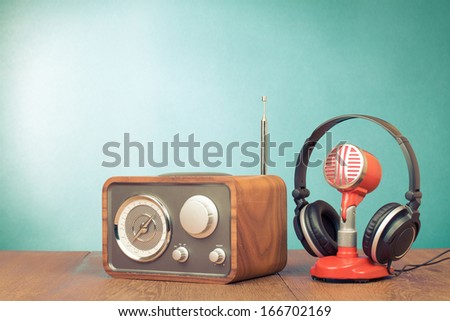 Retro radio, red microphone, headphones on table old style photo - stock photo