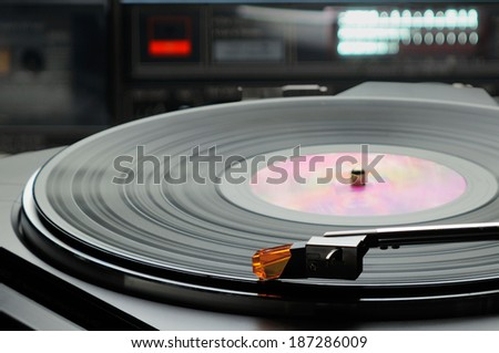 Retro record player turntable with vinyl record (LP) with lit sound level meter meter in background and other electronic equipment. Selective focus. - stock photo