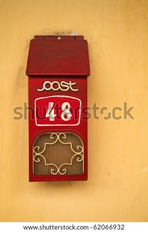Retro red style letterbox with number against yellow wall - stock photo