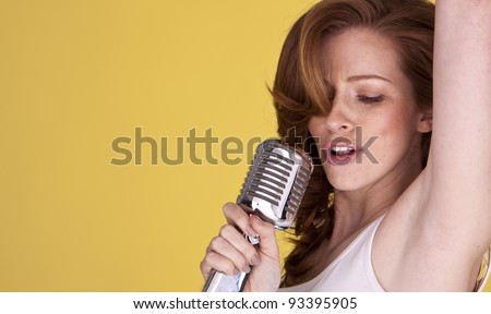 Retro redhead female singer with microphone singing her heart out. Redhead female singer. - stock photo
