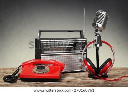 Retro. Retro rotary telephone, radio, headphones, microphone on table - stock photo