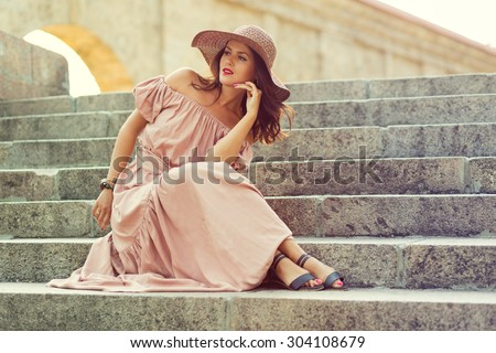 Retro romantic girl in the long dress sitting on the stair - stock photo