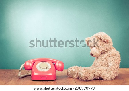 Retro rotary telephone and old Teddy Bear front mint green wall background. Vintage instagram style filtered photo