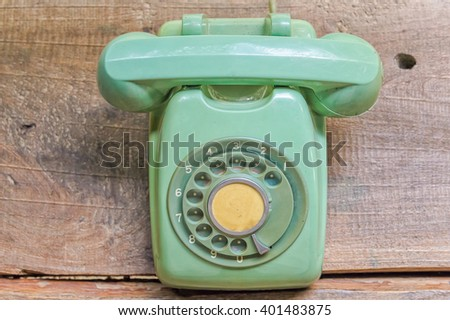 Retro rotary telephone on old wood table - stock photo