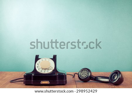 Retro rotary telephone on table in front mint green background. Old instagram style filtered photo - stock photo
