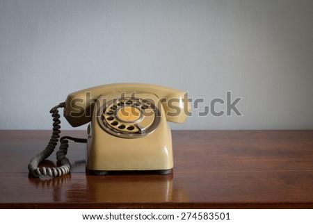 Retro rotary telephone on wood table - stock photo